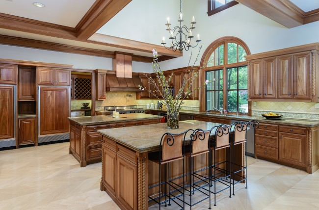 Two granite islands, one with a breakfast counter, offer additional storage and power, while rich cherry cabinetry, windows and ceiling beams lend warmth to the room. Built-in appliances include Viking gas stove with 8-burner cooktop and griddle, copper commercial vent, three ovens, two dishwashers, and separate SubZero refrigerator and freezer.
