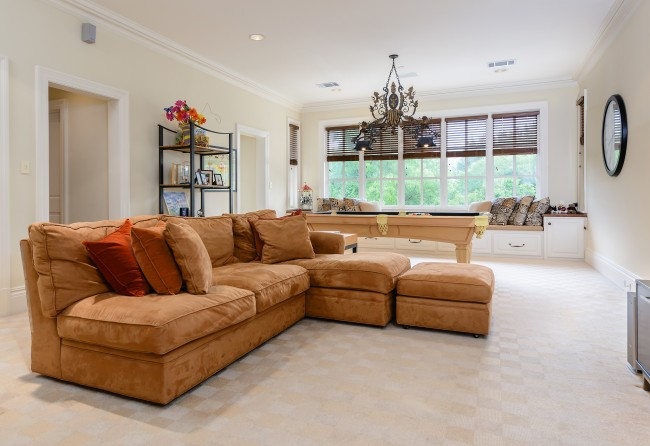 The playroom has a large window seat with a backyard view and a full bath.