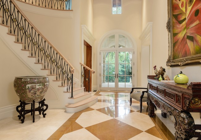 The two-story foyer features polished marble and cross-cut travertine flooring, a circular stone stairway, custom iron balusters with gilded sunflower motif, and maple handrails and stair treads.