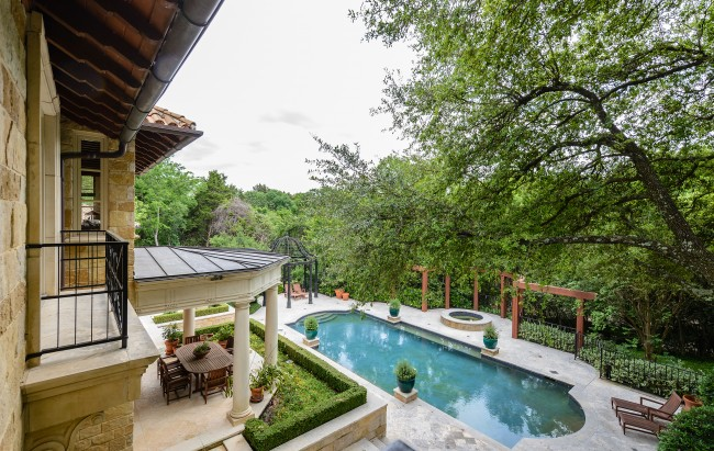 The breathtaking view from one of the upstairs bedrooms includes the poolscape and the creek.