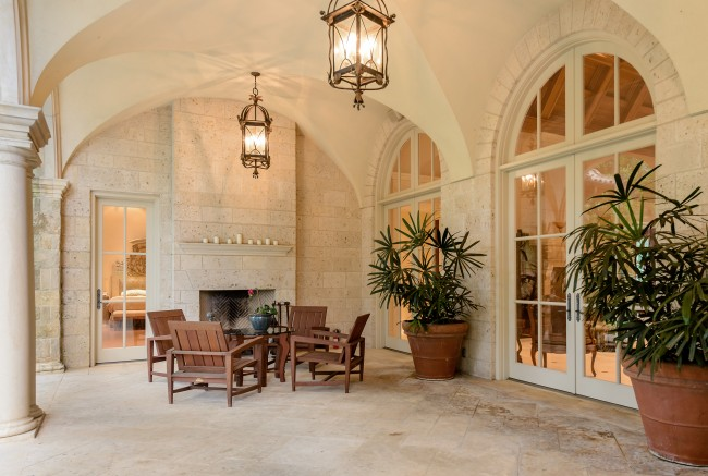 The stone loggia can be accessed from the master suite and features buttressed ceilings and a wood-burning fireplace.