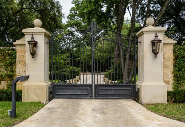 Custom iron gates, stone and iron fencing, and herringbone-pattern Texas limestone surface with stone insets, set the tone for what's to come at 4949 Calleja Way