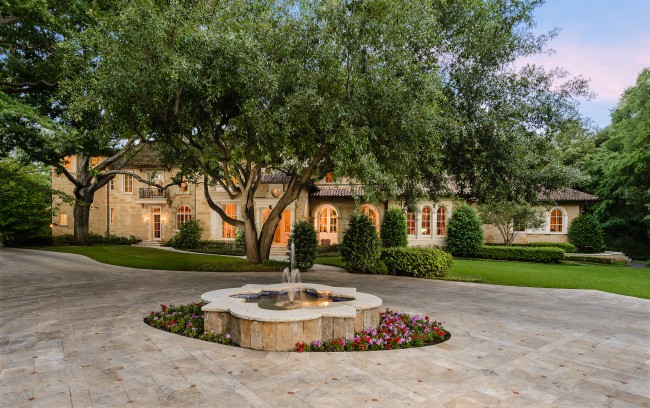 The front circle drive has a stone fountain, plus there's additional parking and a secluded drive around to the five-car garage and exterior entrance to the quarters of 4949 Calleja Way.