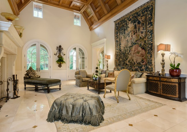 The two-story great room has a maple ceiling, a stone fireplace, custom moldings and French doors opening on to the stone loggia in back and the covered porch in front.