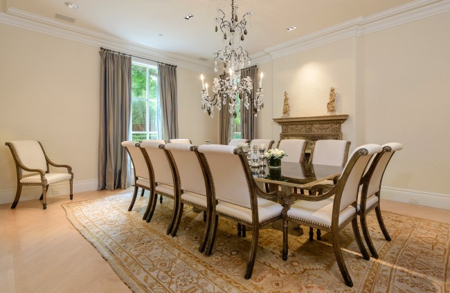 The dining room overlooks the front fountain and boasts a fireplace with unusual Symphony quartz insert, herringbone-patterned maple flooring, and crystal chandelier.