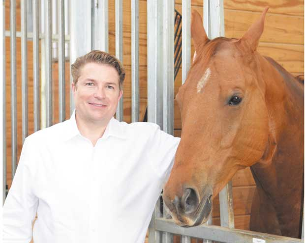 Andy Steingasser stands next to one of Equest's 33 therapy horses.